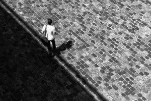 A man walking on the cobblestones and stepping out of the shadow area.